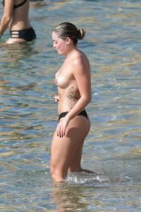 Olympia Valance topless on beach